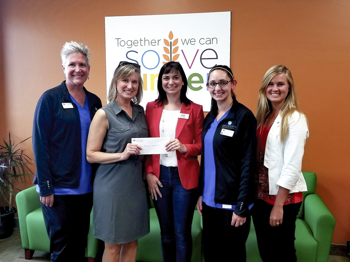 Valley Eye Associates staff members deliver a check to Feeding America