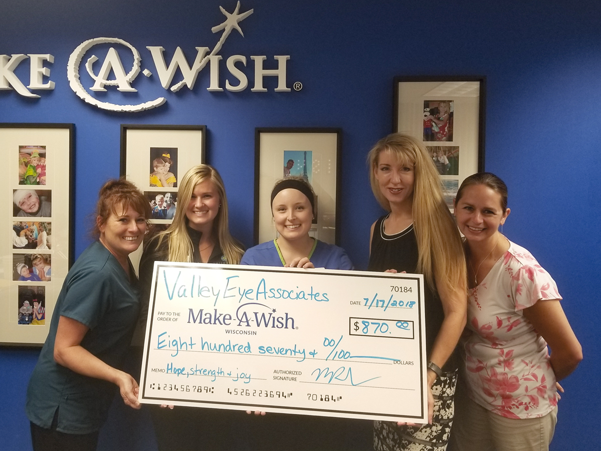 Valley Eye Associates staff members deliver a check to the the Make-A-Wish Foundation