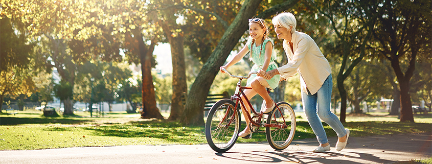 Senior woman teaching her granddaughter how to ride a bike
