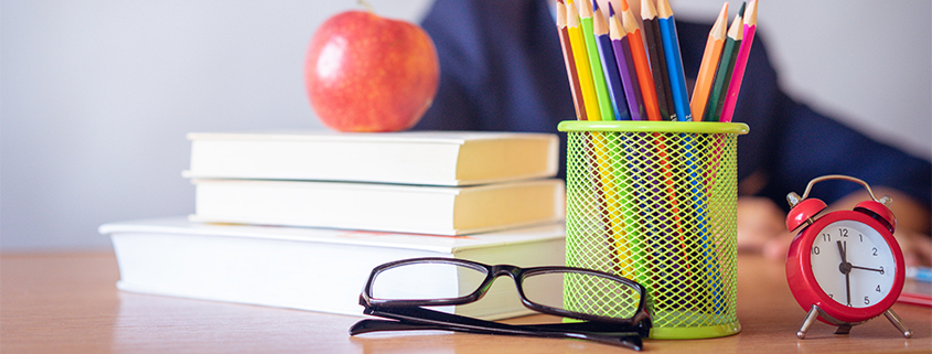 Stack of school supplies and a pair of kids' glasses